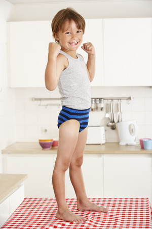 ropa interior: Ni�o de pie en la tabla de cocina En Ropa Interior Foto de archivo
