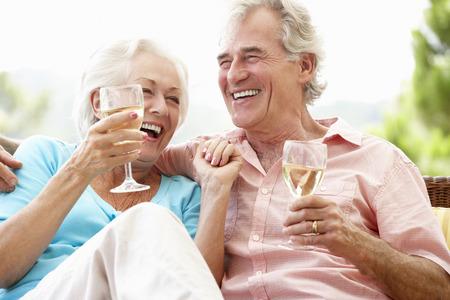 tomando vino: Senior Couple Sitting On Outdoor Seat Together Drinking Wine Foto de archivo