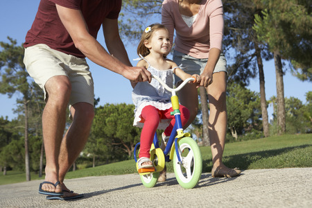 father teaching daughter: Parents Teaching Daughter To Ride Bike In Park