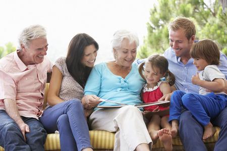 three story: Multi Generation Family Reading Book On Garden Seat