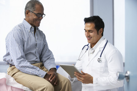hospital notes: Doctor In Surgery With Male Patient Using Digital Tablet Stock Photo