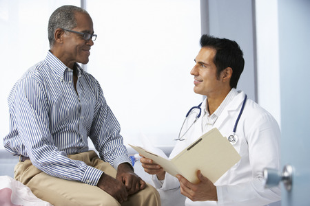 stethoscope: Doctor In Surgery With Male Patient Reading Notes Stock Photo