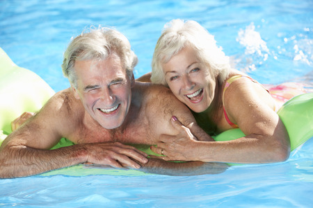 nadando: Pares mayores el d�a de fiesta en piscina Foto de archivo