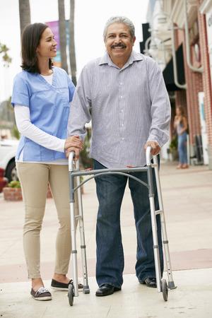 ageing process: Carer Helping Senior Man To Use Walking Frame Stock Photo