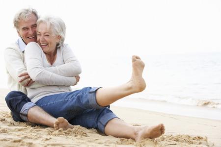 一緒にビーチに座ってシニア カップル