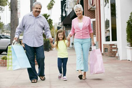 old street: Senior Couple With Granddaughter Carrying Shopping Bags