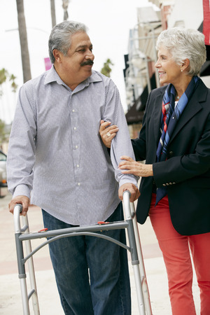 the ageing process: Wife Helping Senior Husband To Use Walking Frame