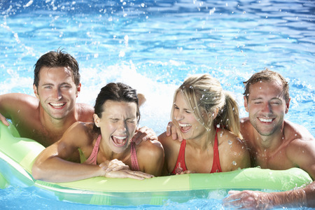 lilo: Group Of Friends On Holiday In Swimming Pool