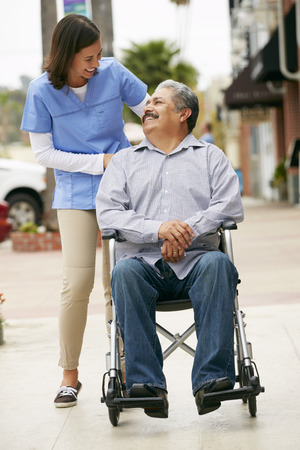 the ageing process: Carer Pushing Disabled Senior Man In Wheelchair