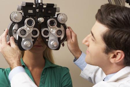 eye exam: Optician In Surgery Giving Woman Eye Test