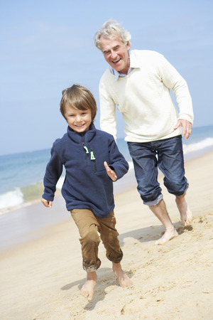 to old clothes: Abuelo y nieto correr a lo largo de la playa