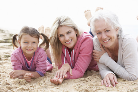 grown ups: Multi Generation Family Lying On Beach Together