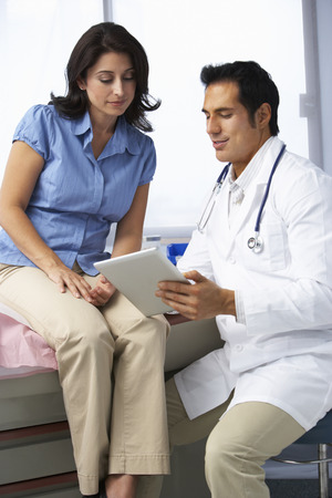 Doctor In Surgery With Female Patient Discussing Notes On Digital Tablet Stock Photo