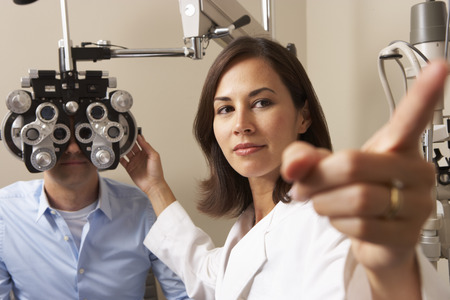 lab test: Female Optician In Surgery Giving Man Eye Test