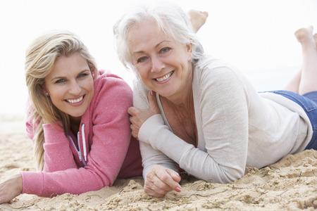 casual hooded top: Mujer mayor con la hija adulta relaja en la playa Foto de archivo