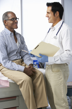 Doctor In Surgery With Male Patient Reading Notes Stockfoto