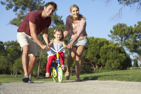 riding: Parents Teaching Daughter To Ride Bike In Park