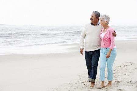 seniors: Senior pareja caminando por la playa juntos