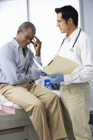 consulta m�dica: Doctor en cirug�a con el paciente masculino leer notas