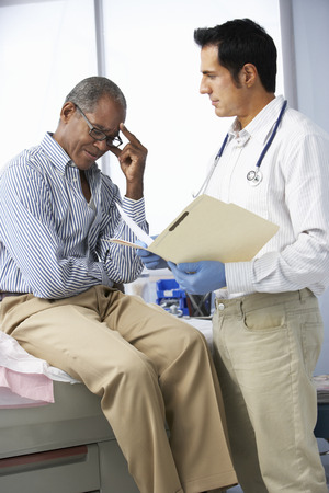 test results: Doctor In Surgery With Male Patient Reading Notes Stock Photo