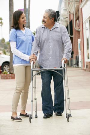 the ageing process: Carer Helping Senior Man To Use Walking Frame Stock Photo