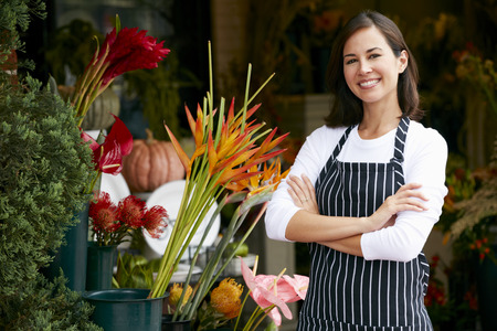 shop window: Portrait Of Female Florist Outside Shop Stock Photo