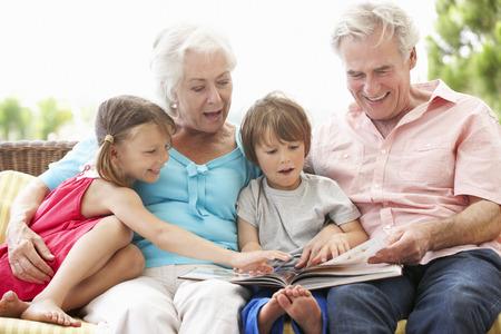 祖父母と孫のガーデン席で本を読んで 写真素材