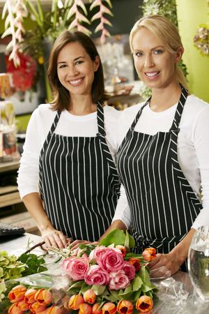 retail store: Portrait Of Two Sales Assistants In Florists Shop Stock Photo