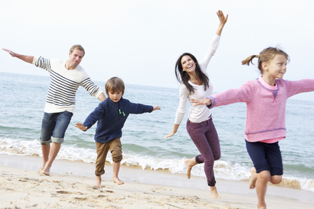 families together: Familia que juega en la playa junto