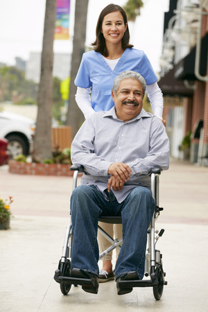 care in the community: Carer Pushing Disabled Senior Man In Wheelchair