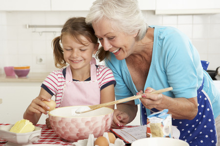 grandparent: Grandmother And Granddaughter Baking In Kitchen