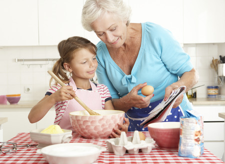 smiling people: Grandmother And Granddaughter Baking In Kitchen