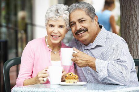 caf: Senior Couple Enjoying Snack At Outdoor Caf�