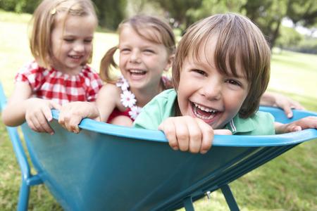three children: Three Children Sitting In Wheelbarrow