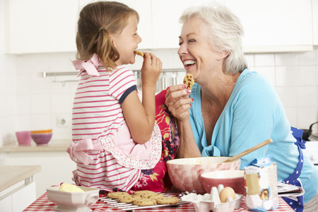 grandmother grandchild: Grandmother And Granddaughter Baking In Kitchen