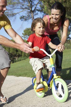 mama e hijo: Los padres que enseñan Hijo montar la bici en el parque