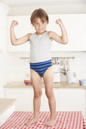 niño de pie: Niño de pie en la tabla de cocina En Ropa Interior Foto de archivo