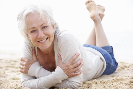 relajado: Mujer mayor que se relaja en la playa Foto de archivo