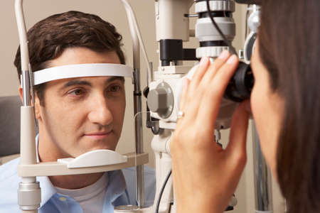 optician: Female Optician In Surgery Giving Man Eye Test