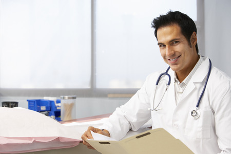 record: Male Doctor In Surgery Reading Patient Notes