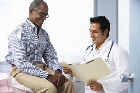 닥터 외과 남자 환자 읽기 노트와 함께 스톡 콘텐츠