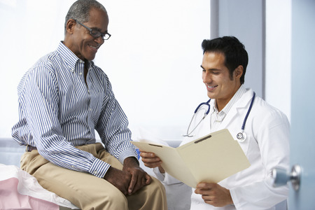 exam results: Doctor In Surgery With Male Patient Reading Notes Stock Photo