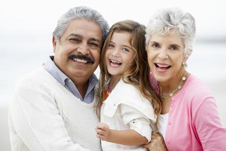 Portrét prarodičů na pláži s vnučkou