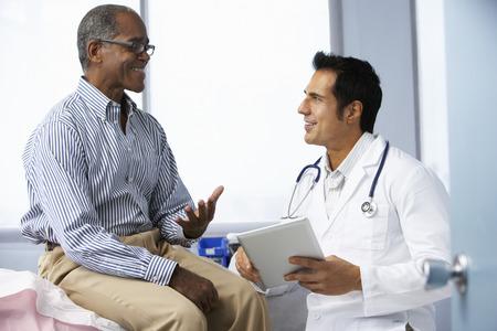 consulta médica: Doctor en cirugía con el paciente masculino que usa la tablilla digital