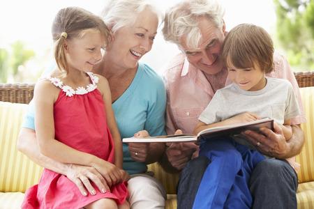 조부모와 손자 정원 가든에 책을 읽고 스톡 콘텐츠