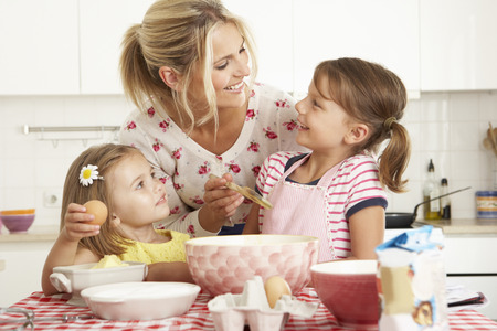 stirring: Mother And Two Girls Baking In Kitchen