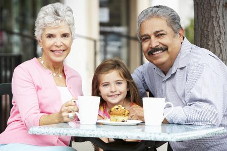 caf: Grandparents With Granddaughter Enjoying Snack At Outdoor Caf�