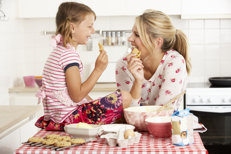 eating pastry: Mother And Daughter Baking In Kitchen