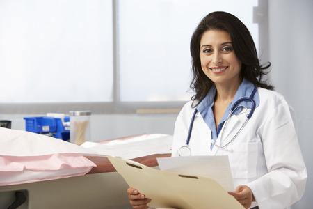 medical doctors: Female Doctor In Surgery Reading Patient Notes