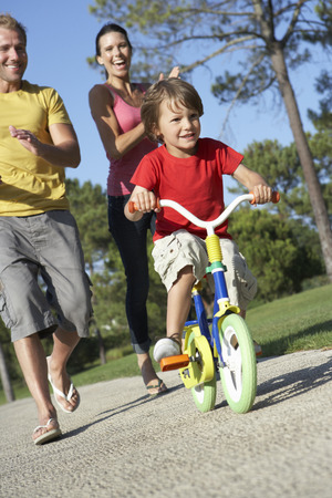 teaching: Parents Teaching Son To Ride Bike In Park Stock Photo